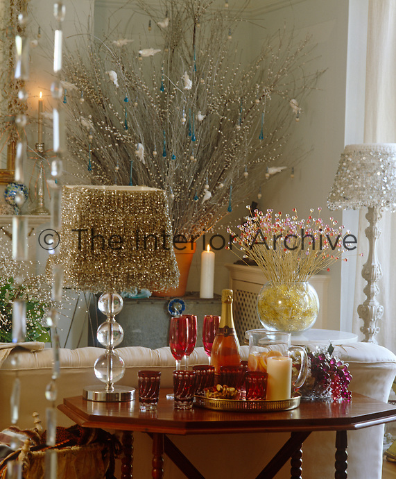 A bottle of pink champagne sits on a side table in a living room full of sparkling Christmas decorations