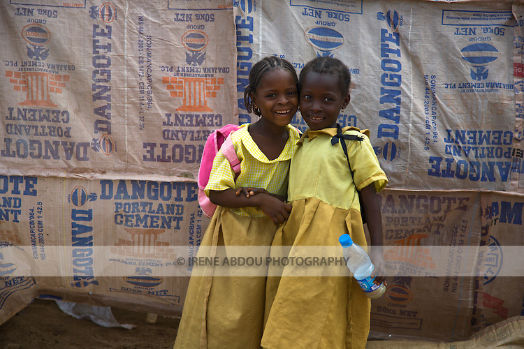Children walk home from school through the Durumi market area of Abuja, Nigeria.