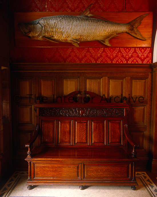 A carved bench in the panelled entrance hall is placed beneath a huge trophy of a salmon