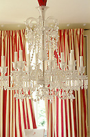 An opulent Baccarat creation in faceted crystal drops hangs in this living room against the backdrop of a set of red and white striped silk curtains