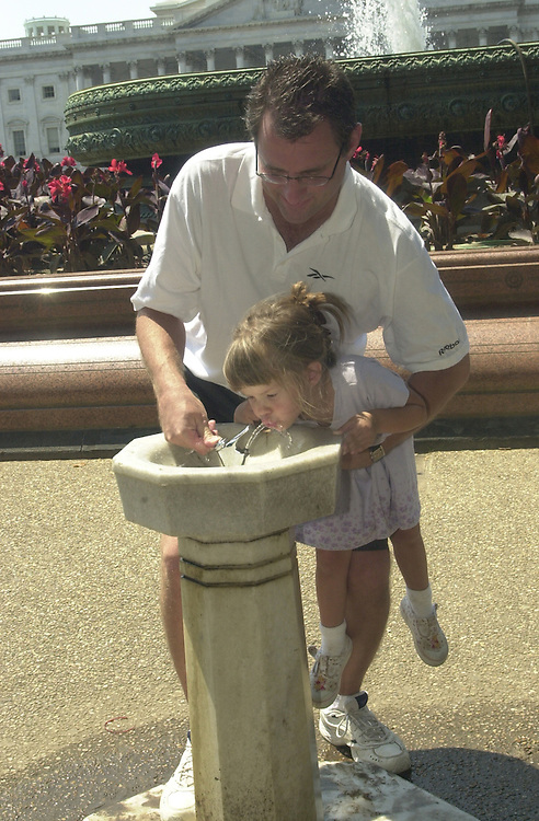 2feature080701 -- Amanda Snell, 4, of Shawnee, Kansas, gets a boost from her father Dan, on a sweltering, sultry Tuesday in August.