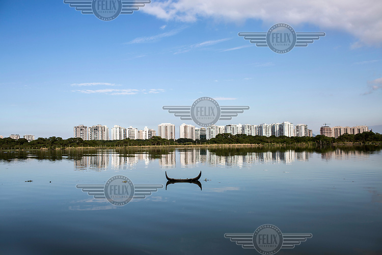 A car's bumber floats in the sewage infested water of Lagoa da Tijuca, one of several interconnected lagoons in Barra da Tijuca. <br /> <br /> As developement in the area increases so too does the raw sewage and pollution in the district's lakes.<br />  <br /> <br /> The authorities and private developers have poured billions of dollars into transportation projects, hotels, a residential complex to house the athletes and a vast Olympic Park where nearly half the sports will be played in Rio's expansive neighbourhood, Barra da Tijuca. <br /> <br /> Those improvements join the private schools, gated communities, and other consumer culture that attracts middle-class families tired of run-down feel of Rio's older neighbourhoods. <br />  <br /> However, the breakneck development has brought problems similar to those of which its new residents were fleeing, including congested traffic and untreated sewage in what was supposed to be a new model for urban living.