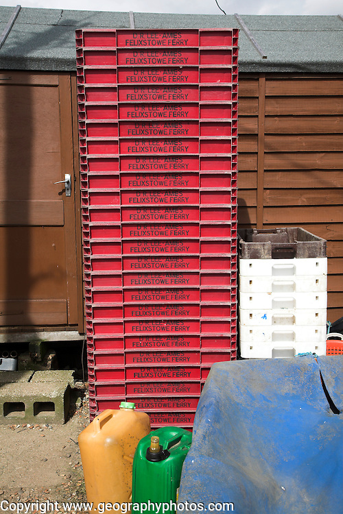 Plastic fish crates stacked. Small fishing and sailing hamlet of Felixstowe Ferry at the mouth of the River Deben, Suffolk, England