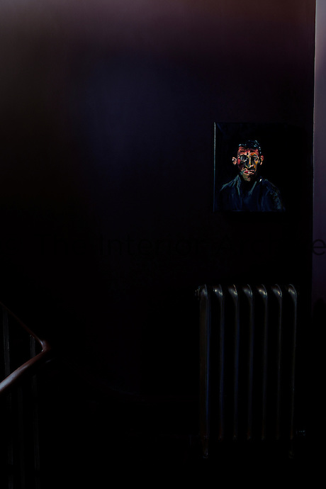 A detail of a dark purple room with a portrait painting just seen in shadow hanging above a traditional radiator