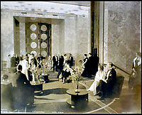 BNPS.co.uk (01202 558833)<br /> Pic:    CanterburyAuctionGalleries/BNPS<br /> <br /> Guests mingle in the foyer of B Deck.<br /> <br /> Remarkable photos of the iconic ocean liner SS Normandie which was like a 'floating palace' have come to light over 80 years later.<br /> <br /> The giant 1,000ft long French passenger ship was the largest of her type in the world and won the coveted 'Blue Riband' for the fastest crossing of the Atlantic.<br /> <br /> English photographer Percy Byron's photos show the liner's luxurious 'Art Deco' interior with its chandeliers and pillars of Lalique glass.<br /> <br /> The vessel, which launched in 1935, even boasted its own swimming pool and a gym where young women can be seen doing aerobics while a man in a suit trains with a punch bag.