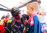 Oct 18, 2019; Ennis, TX, USA; NHRA top fuel driver Antron Brown (left) signs an autograph on a young fans shirt during qualifying for the Fall Nationals at the Texas Motorplex. Mandatory Credit: Mark J. Rebilas-USA TODAY Sports