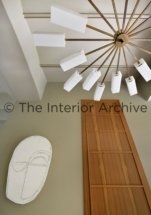 A view looking up to a contemporary light fitting hanging from the cieling. A wood panel and a piece of modern art are displayed on the wall.
