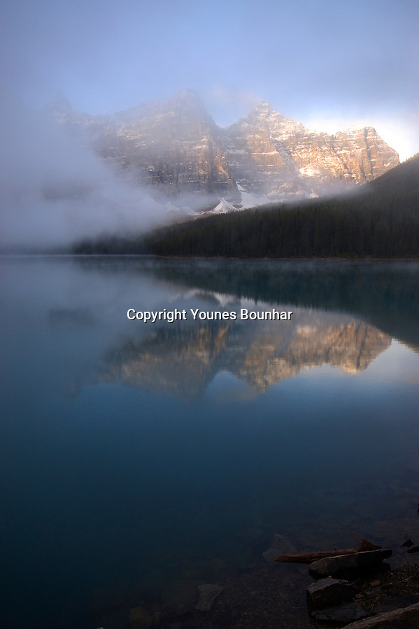 Fog rises as valley of ten peaks is reflected on the turquoise surface of beautiful Moraine Lake
