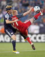 Toronto FC defender Richard Eckersley (27) clears the ball away from New England Revolution midfielder Pat Phelan (28). In a Major League Soccer (MLS) match, the New England Revolution tied Toronto FC, 0-0, at Gillette Stadium on June 15, 2011.