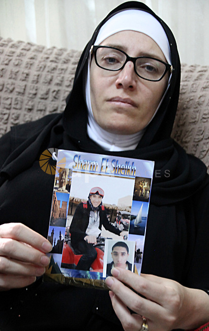 The mother of the 18-year-old Palestinian Mustafa al-Khatib, who was killed by Israeli security forces, holds his picture at their house in Jabal al-Mukaber neighborhood, southern Jerusalem, on October 13, 2015. A wave of stabbings that hit Israel, Jerusalem and the West Bank this month along with violent protests in annexed east Jerusalem and the occupied West Bank, has led to warnings that a full-scale Palestinian uprising, or third intifada, could erupt. The unrest has also spread to the Gaza Strip, with clashes along the border in recent days leaving nine Palestinians dead from Israeli fire. Photo by Mahfouz Abu Turk