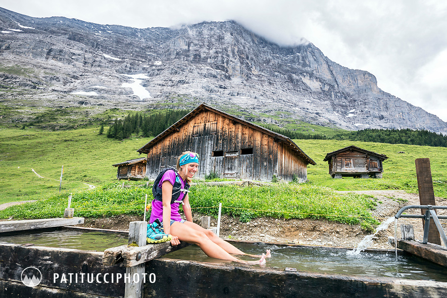 A woman trail runner sits with her feet in a water fountain above Grindelwald, Switzerland