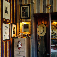 A corner of a masculine bedroom with hand-painted striped walls