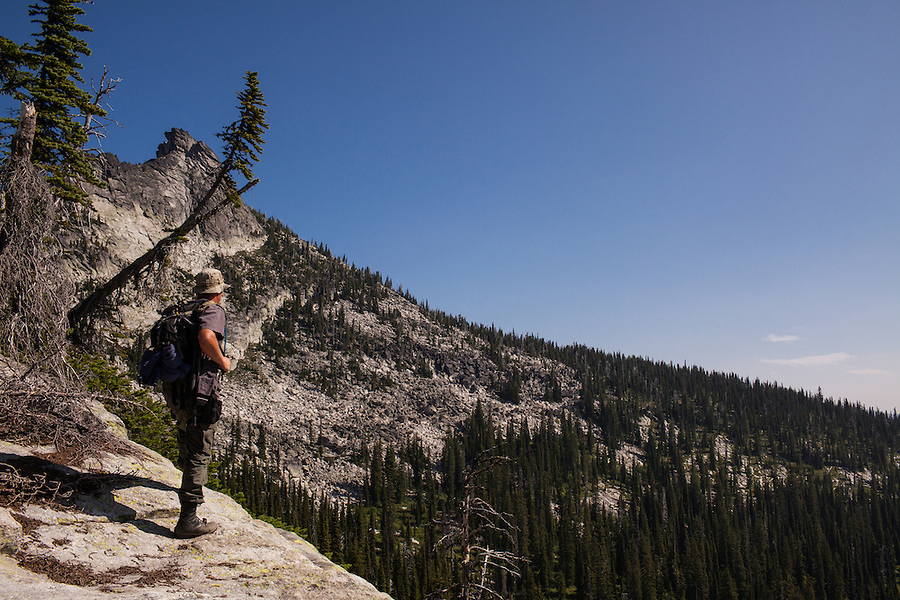 A man in his mid-30's looks over the edge of a cliff towards Harrison Peak in the Selkirks of Northern Idaho.