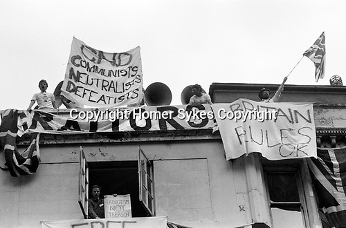 Pro supporters of the Falkland war hang banners from a Whitehall building London, as an anti falklands war demo passes underneath. London May 1983. 'CND <br />