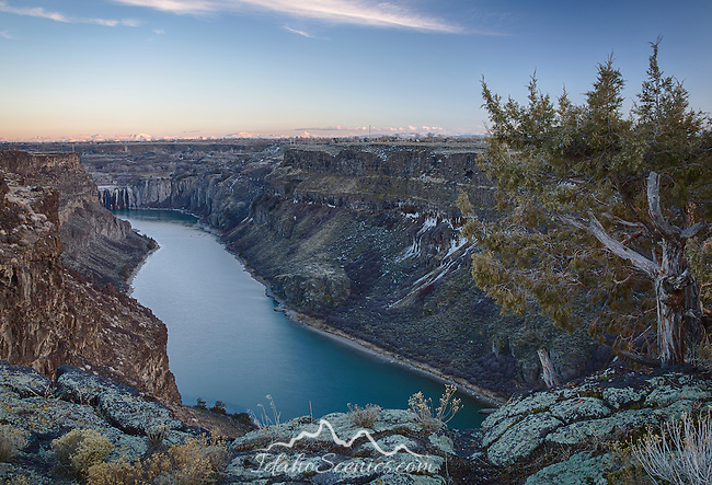 Idaho, South Central, Twin Falls.  The Snake River Canyon from the north rim in evening with Shoshone Falls inthe distance in winter.