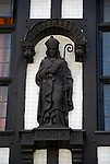 Statue of Walkelin, the first Norman Bishop of Winchester on exterior of Tudor building in Winchester High Street, England