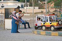 Tripoli, Libya, North Africa - Libyan Parents Waving to Child on Amusement Park Ride.