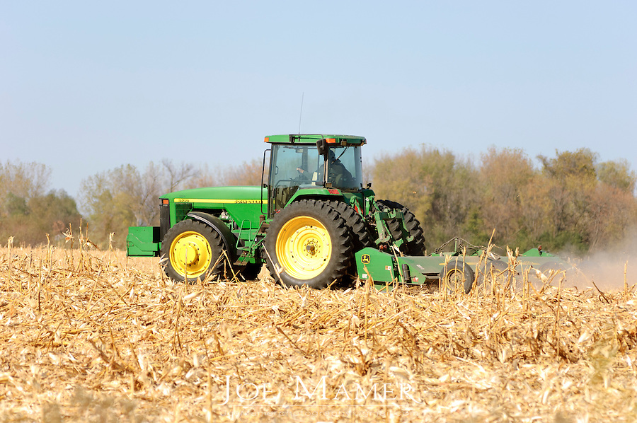 A tractor pulls a stalk chopper to cut down corn stalks prior to cultivating the field.
