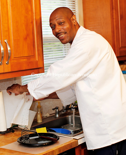 Waterbury, CT- 23, July 2010-072310CM08 Mark Yates stops to clean while preparing a meal for family and friends inside his Waterbury home. Yates, is in the process of starting his own catering business with the help from Small Business Development Center and New Opportunities Inc.  --Christopher Massa Republican-American