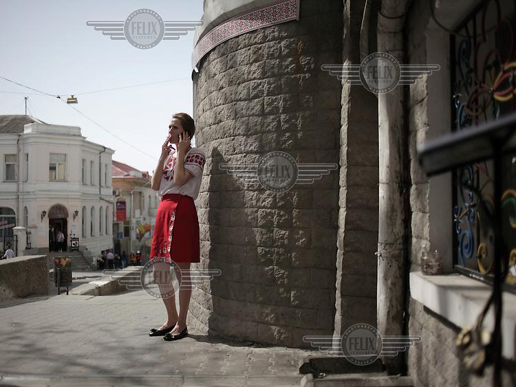 A waitress smokes as she takes a break outside a restaurant in Sevastopol.