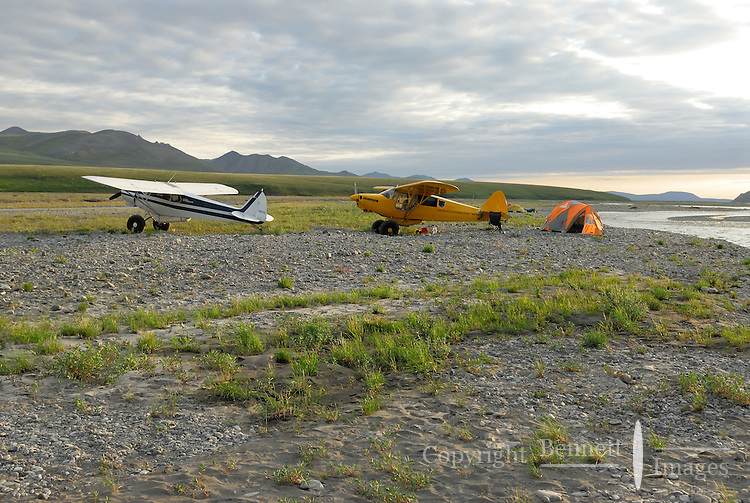 Two Piper Super Cubs are lit by the evening sun along the Kongakut River, in Alaska's Arctic National Wildlife Refuge.