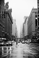 Pedestrian with an Umbrella Runs to cross the street on a Rainy Day in Downtown Chicago, IL