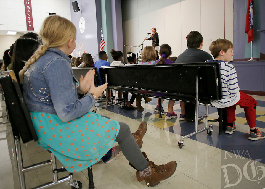 NWA Democrat-Gazette/DAVID GOTTSCHALK  Lily Kay (left) claps and pats her foot Tuesday, October 6, 2015 while listening to Joe Crookston perform on stage for the fifth grade students at Holt Middle School in Fayetteville. Crookston performed and led workshops in the area for the past week as part of the True Lit Festival.