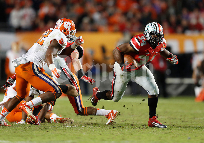 Ohio State Buckeyes running back Carlos Hyde (34) breaks away from the Clemson Tigers defense for a big gain on a fourth down in the third quarter of the Discover Orange Bowl between Ohio State and Clemson at Sun Life Stadium in Miami Gardens, Florida, Friday night, January 3, 2014. As of the fourth quarter the Ohio State Buckeyes led the Clemson Tigers 35 - 34.(The Columbus Dispatch / Eamon Queeney)