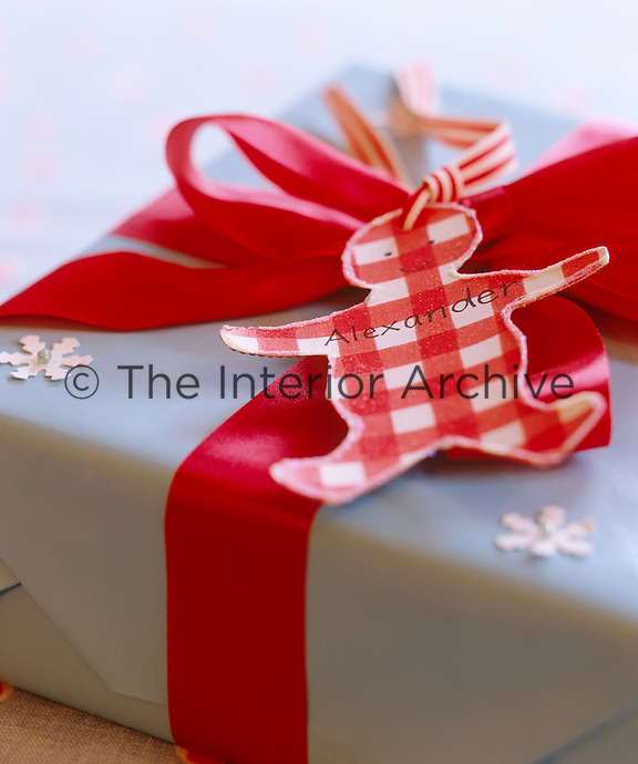 A label in the shape of a ginger bread man has been attached to this present with a red ribbon