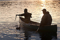 Waterfowl hunters set decoys at dusk from a canoe.