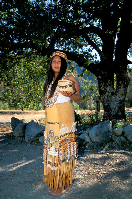 Full shot of a traditional Yurok girl; (11yrs old); poses in a traditional leather skirt decorated with shells; seeds and woven grass. Jene also is wearing traditional beaded shell necklaces and a basket woven hat. She is also holding a grass woven basket with lid. Hoopa Valley Indian Reservation; California