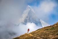 Trail running above Zermatt, Switzerland as the clouds part revealing the Matterhorn.