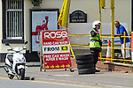 © Joel Goodman - 07973 332324 . 19 June 2013 . A635 Ashton Old Road , Openshaw , UK . The warden talks with the business owner about the parked car . A traffic warden parks his motorbike on a double yellow line in order to issue a ticket to a vehicle parked on the pavement on Ashton Old Road today (Wednesday 19th June) . Photo credit : Joel Goodman