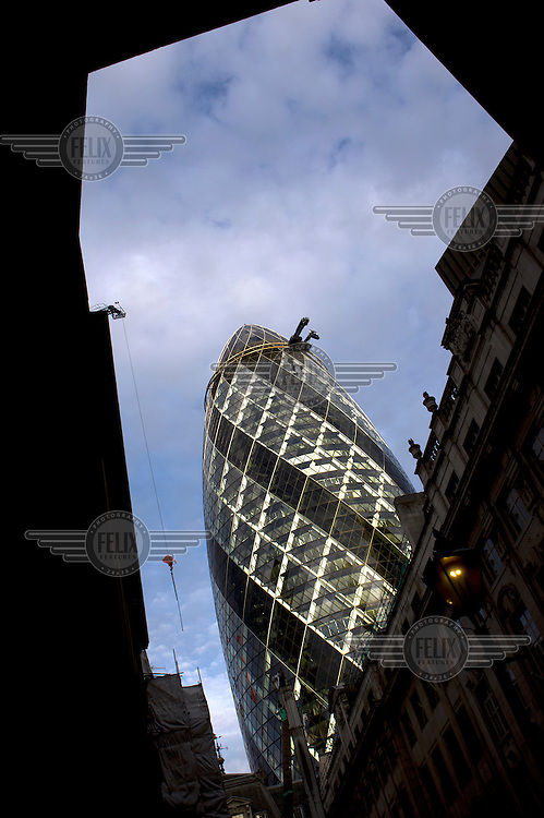 30 St Mary Axe (Swiss Re Tower, The Gherkin) seen from St Helen's Place off Bishopsgate in the City of London. The tower was, in 2012, London's seventh tallest building at 179.9 metres. The architects were Norman Foster and Partners and it was finished in 2003.
