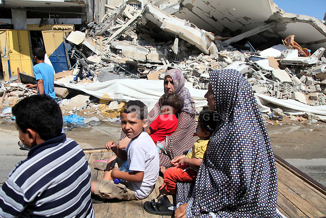 """Palestinians ride a donkey cart past destroyed houses in Gaza city on August 10, 2014. A senior Hamas official said there was a """"weak"""" possibility that Gaza truce talks would succeed and that Palestinian negotiators could leave Cairo after a meeting with Egyptian mediators. Photo by Ezz al-Zanoun"""