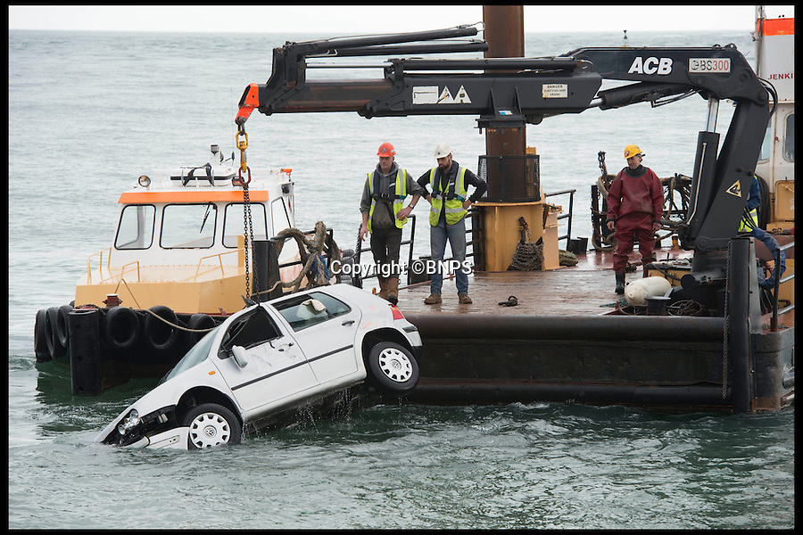 BNPS.co.uk (01202 558833)<br /> Pic: LauraDale/BNPS<br /> <br /> The car being lifted from the water.<br /> <br /> An elderly woman has today been rescued from her sunken car after she 'deliberately' drove into a harbour in front of stunned 