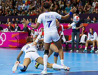 28 JUL 2012 - LONDON, GBR - Heidi Løke (NOR) of Norway (right, in red) finds her path to goal blocked by Nina Kamto Njitam (FRA) (left, in white) and Allison Pineau (FRA) of France (centre, in white) during their women's London 2012 Olympic Games Preliminary round handball match at The Copper Box in the Olympic Park, in Stratford, London, Great Britain (PHOTO (C) 2012 NIGEL FARROW)