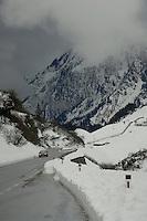 Car travelling through alpine pass, with low cloud above mountains. St Anton, Tyrol / Tirol, Austria.