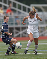 Seacoast United Phantoms player Michelle Trembley (27) and Boston Aztec midfielder/defender Alex Bengston (9) battle for the ball.  In a Women's Premier Soccer League (WPSL) match, Boston Aztec (white) defeated Seacoast United Phantoms (blue), 3-0, at North Reading High School Stadium on Arthur J. Kenney Athletic Field on on June 25, 2013.