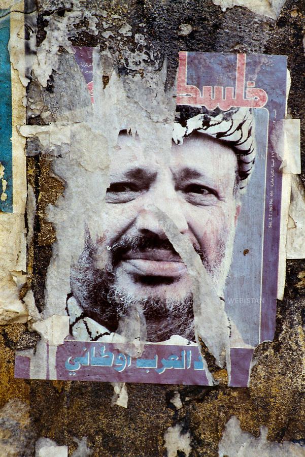 1983. Lebanon. Tripoli. Torn poster of a portrait of Yasser Arafat (1929-2004), chairman of the PLO, during the Lebanese War (1975-1990). Liban. Tripoli. Poster déchiré d'un portrait de Yasser Arafat (1929-2004), le chef de l'OLP, pendant la Guerre du Liban (1975-1990).