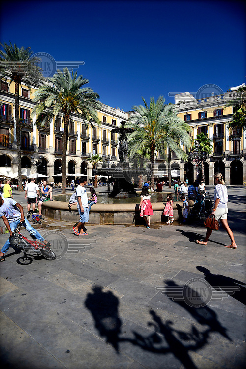 Visitors sit around the fountain in Placa Reial. /Felix Features