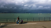 A young family stroll by the sea while a thick black cloud hangs over the city of Swansea as seen from sunny Mumbles on the opposite side of the bay in south Wales, UK. Sunday 25 June 2017