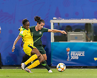 GRENOBLE, FRANCE - JUNE 18: Sashana Campbell #12 of the Jamaican National Team, Lisa De Vanna #11 of the Australian National Team battle for the ball during a game between Jamaica and Australia at Stade des Alpes on June 18, 2019 in Grenoble, France.