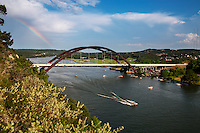 A beautiful rainbow towers over the 360 Bridge as boaters take to the waters of Lake Austin in west Austin, Texas.