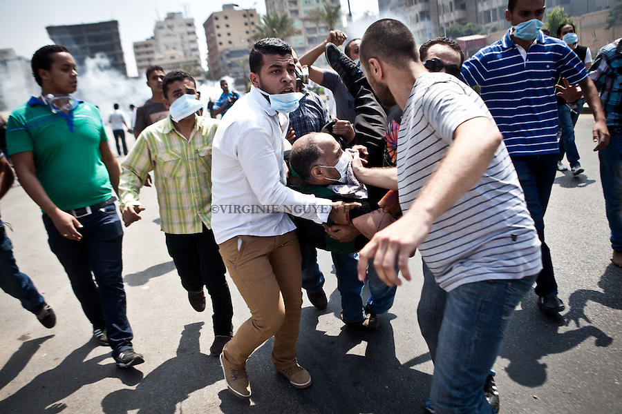 Des manifestants portent un homme bless&eacute; lors d'affrontements avec la police dans la rue Tayaran pr&egrave;s de Rabaa square, Nasr city, Le Caire, Egypte, le mercredi 14 ao&ucirc;t 2013.<br /> <br /> Protesters carrying a wounded man during clashes with police in Tayaran steet near Rabaa square, Nasr city, Cairo, Egypt, Wednesday, August 14, 2013.