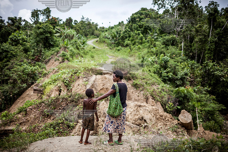 Martha Wokma, 49, stranded, with her nephew, beside a collapsed bridge that was used by illegal loggers to bring timber out of the forest. Martha says: 'We can't take this road anymore, we can't visit our relatives and friends in other villages. The logging company made big damage to our village and environment and they never paid any compensation.' Illegal logging is having a telling environmental impact on PNG. Logging companies often corruptly obtain permissions to cut timber from its forests, and they usual operate without controls, destroying ecosystems and local people's lives.