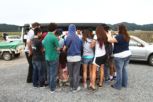 June 20, 2012; Ishinomaki, Miyagi Pref., JPN - Tohoku recovery. ..In front of Okawa Elementary School, where 74 of 108 students and 10 of 13 teachers died from the March 11 tsunami, students on the Terasaki Foundation Japan Educational Tour gather around Yasukichi Takeyama as he shows pictures and tells stories about his hometown of Nagatsura. ..Nagatsura is scheduled for demolition despite the fact that more than 30 people are still missing and on June 13, two more bodies were found more than 15 months after the disaster. the residents urgently need volunteers to help search the area for those still missing.