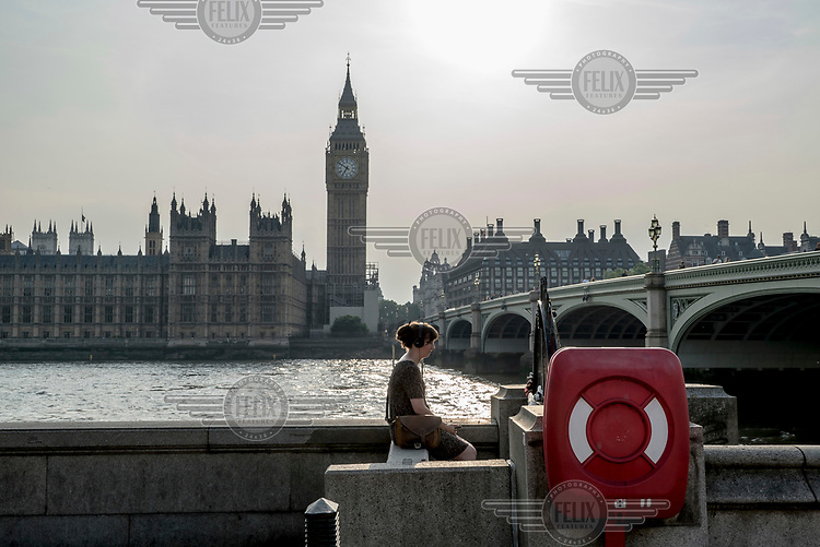 A woman sits on a wall on the South Bank of the Thames, behind her is Westminster Bridge and the Houses of Parliament.