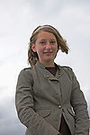 Portrait smiling young teenage girl in winter coat, UK outdoors looking down great overcast background