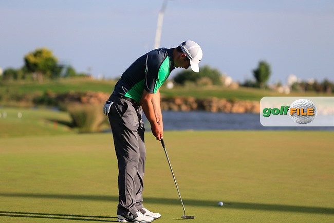 Ross Fisher (ENG) putts on the 18th green during Saturday's Round 3 of the 2013 Portugal Masters held at the Oceanico Victoria Golf Club. 12th October 2013.<br /> Picture: Eoin Clarke www.golffile.ie